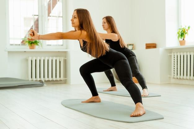 Растяжка тренировки. группа молодых девушек в черной форме делает растяжку в тренажерном зале. акройога, йога, фитнес, тренировки.