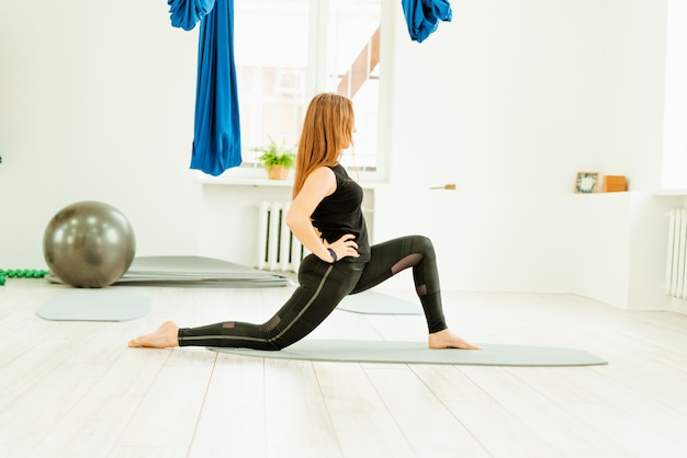 ストレッチ運動。健康的な生活様式。黒い制服を着た美しい少女は、ストレッチ運動をしています。アクロヨガ、ヨガ、フィットネス、トレーニング、スポーツ。