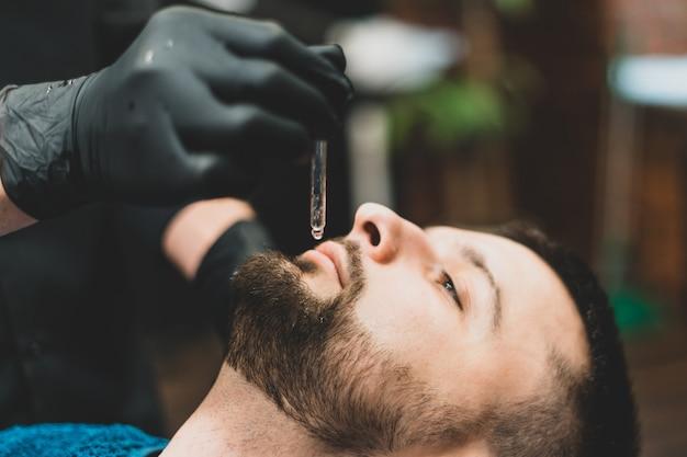 理髪店。理髪店の達人のクライアントである理髪師は、クリエンひげにオイルと化粧品を塗ります。男性の美容室。健康的なライフスタイルと美しさ。