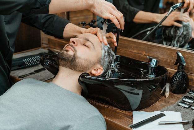 Парикмахерская, мужчина моет волосы. парикмахерская моет своего клиента. вымойте волосы и бороду после стрижки. личная гигиена