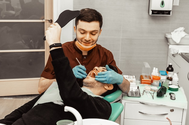 若い男性の歯科医師が患者を治療します。歯科、手術における医療操作。プロの制服と歯科医の機器。ヘルスケア医師の職場を装備。歯科