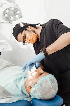 Пациент и стоматолог во время установки имплантата. реальная операция. удаление зубов, имплантаты. профессиональная форма и оборудование стоматолога. здравоохранение оснащение врача рабочим местом. лечение зубов
