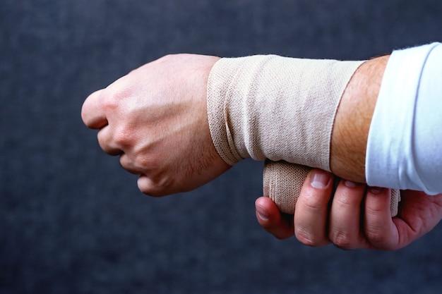 男はスポーツ包帯で手を包帯します。