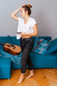 Творчество. девушка художника музыканта в творческом поиске. стоит возле дивана с гитарой. окрашивается краской.