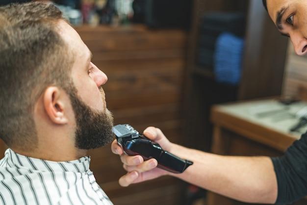 Салон красоты для мужчин. брить бороду в парикмахерской. парикмахер подстригает бороду бритвой и машинкой для стрижки. заделывают брутальные стрижки. парикмахерское оборудование. выборочный фокус.