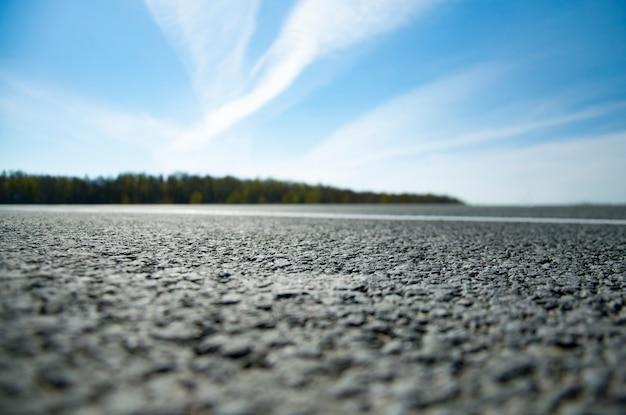 絵のような風景と道路上の日の出。マーキングのあるアスファルト道路。ぼかし付き。