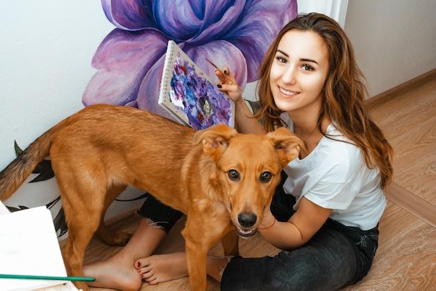 Исполнитель. дизайнер. домашние питомцы. художник маленькой девочки красит на стене внутри помещения. работает и играет с собакой. лечение домашних животных. дизайн интерьера. творческий процесс.