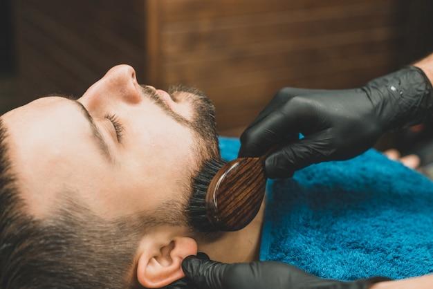 理髪店で散髪ヘッドとひげ。理容師はクライアントのひげを身に着けて櫛でとかす男性向けのヘアスタイルを作成し、ひげをスタイリングするプロセス。理髪店の男。機器スタイリスト。セレクティブフォーカス