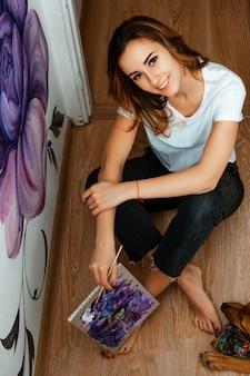 Исполнитель. дизайнер. художник маленькой девочки красит на стене внутри помещения. дизайн интерьера. творческий процесс.