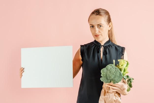 健康的な生活様式。女の子はブロッコリーと緑の野菜を手に持っています。食事と適切な栄養。 。
