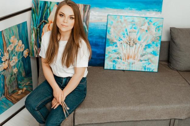 アート、アーティストの作品。美しい少女アーティストは絵を描きます。アーティストのワークショップ。創造性のプロセス。描画とペイント。アーティストの目録。閉じる。