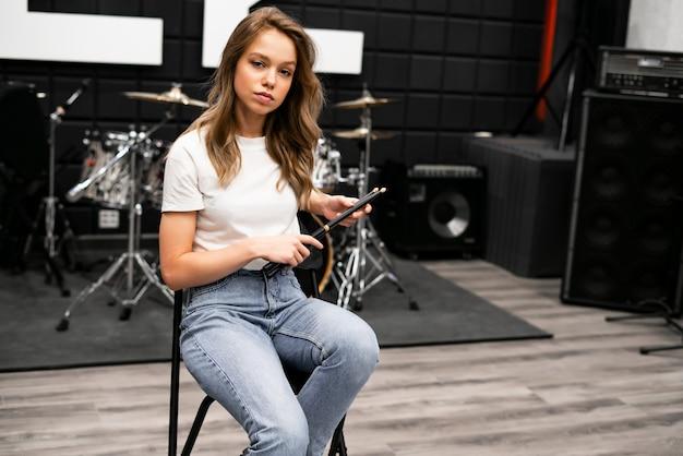 Творчество и музыка. молодая красивая девушка играет на барабанах. звукозаписывающая студия. музыкальное оборудование.