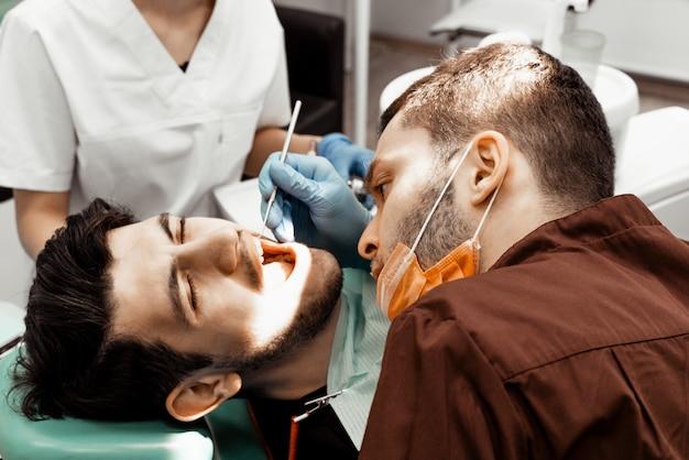 若い男性の歯科医師が患者を治療します。歯科、手術における医療操作。プロの制服と歯科医の機器。ヘルスケア医師の職場を装備します。歯科