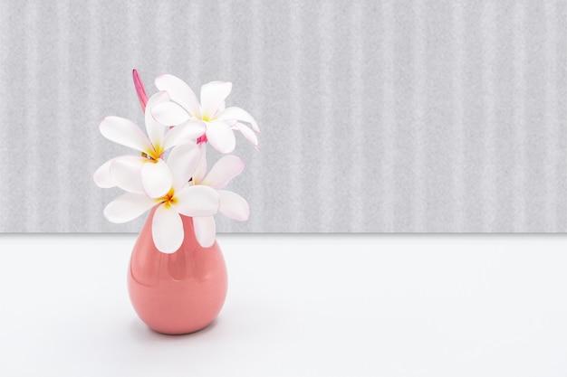Цветы в розовой вазе на сером фоне.