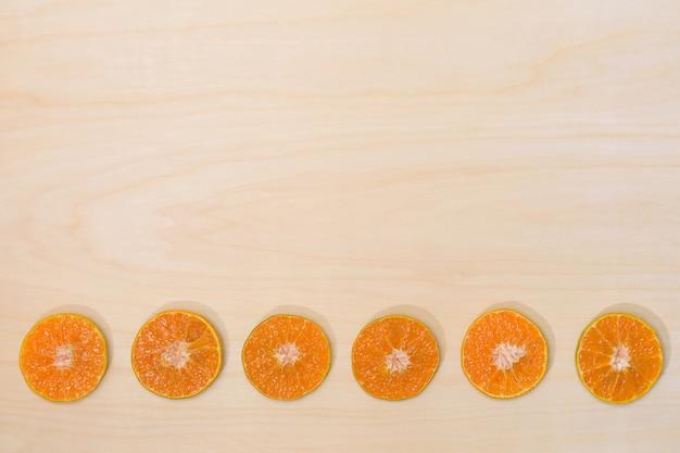 Оранжевый неполный вырубка плодоовощ на деревянной поверхностной предпосылке.