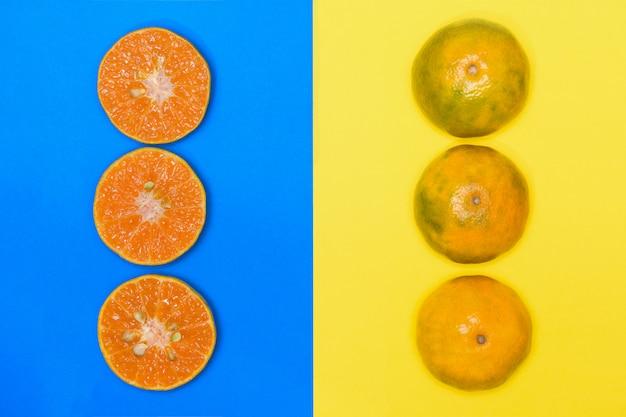 Плод апельсина на желтом фоне и апельсин
