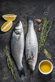 Свежая рыба сибас и ингредиенты для приготовления, лимон и розмарин. темный фон вид сверху.