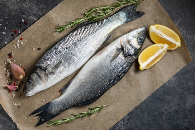 新鮮な魚のシーバスと料理の材料、レモン、ローズマリー。暗い背景のトップビュー。