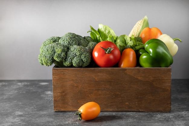 暗い背景の木の木製の箱で新鮮な野菜