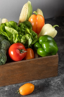 Свежие овощи в деревянной коробке на темном деревянном фоне