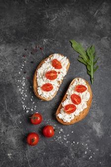 暗いテーブルの上のトマトとチーズのブルスケッタ。上面図