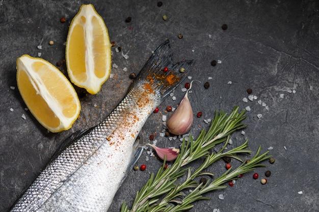 Свежая рыба сибас и ингредиенты для приготовления, лимон и розмарин
