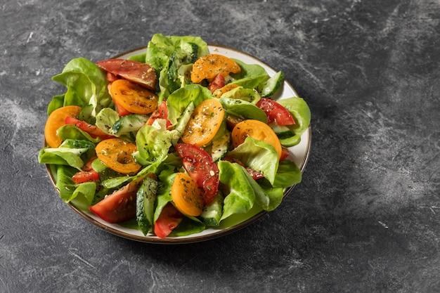 トマト、きゅうり、玉ねぎ、ほうれん草、レタスの新鮮野菜のヘルシーな野菜サラダ。ダイエットメニュー。上からの眺め。