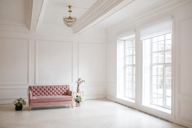 エレガントでクラシックな家具と壁の装飾が施された豪華で豪華なリビングルームのインテリアデザイン。大きな窓と大きな明るい白い部屋