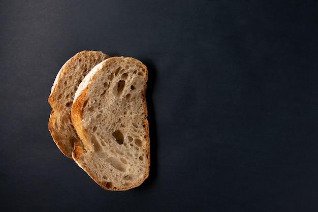 黒い表面に焼きたてのパン。上からの眺め