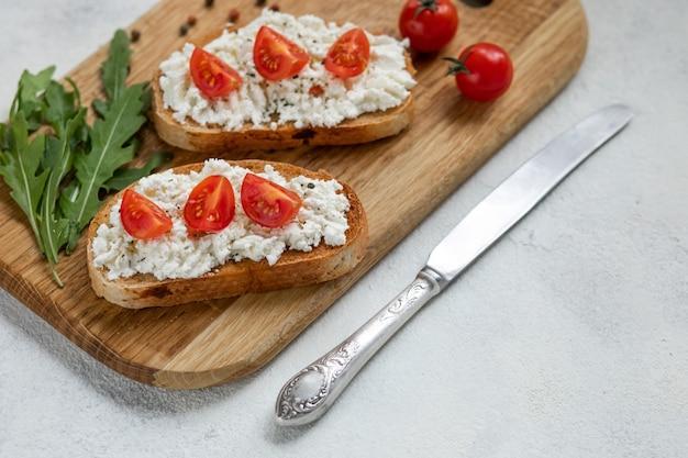 ローストトマト、モッツァレラチーズ、まな板の上のハーブとイタリアのブルスケッタ。