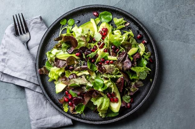 Салат из латука с гранатом на черной тарелке. вид сверху