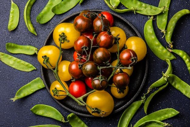 黒の鋳鉄黒パテとグリーンピースの赤と黄色のトマト