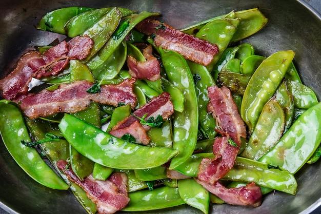 金属の鍋でベーコンと揚げエンドウ豆の鞘