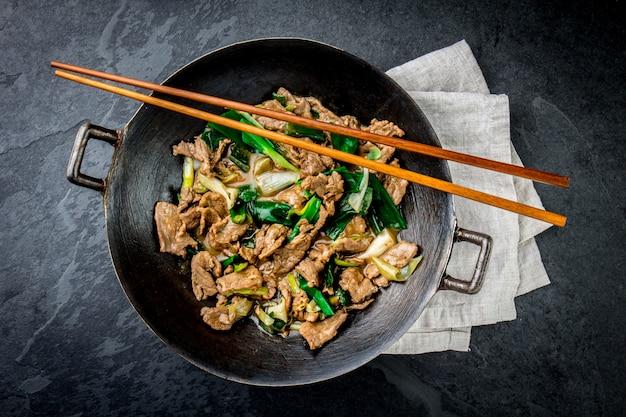 Традиционная китайская монгольская говядина обжаривается в китайском чугунном воке с кулинарными палочками