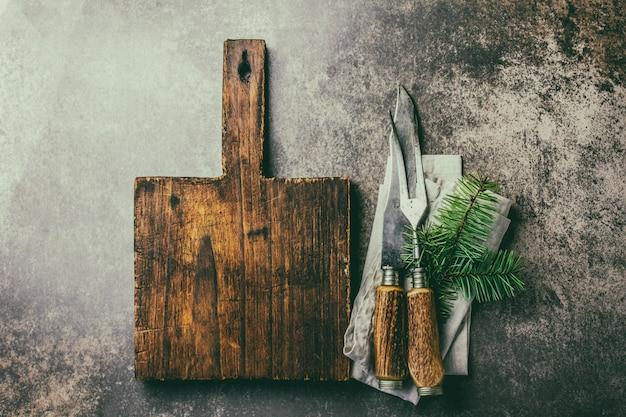 Старинный деревенский набор столовых приборов и деревянная разделочная доска