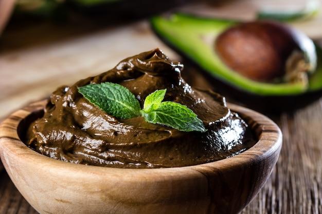 オリーブの木製ボウルにアボカドチョコレートムース