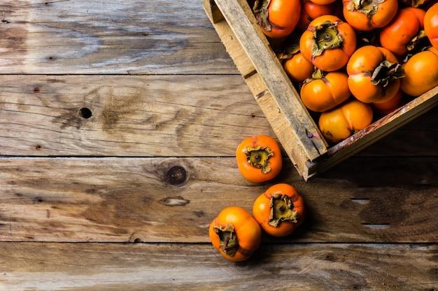 Коробка свежих фруктов хурмы каки на деревянных фоне
