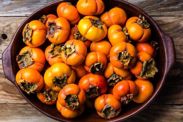Горшок свежих фруктов хурмы каки на деревянном фоне