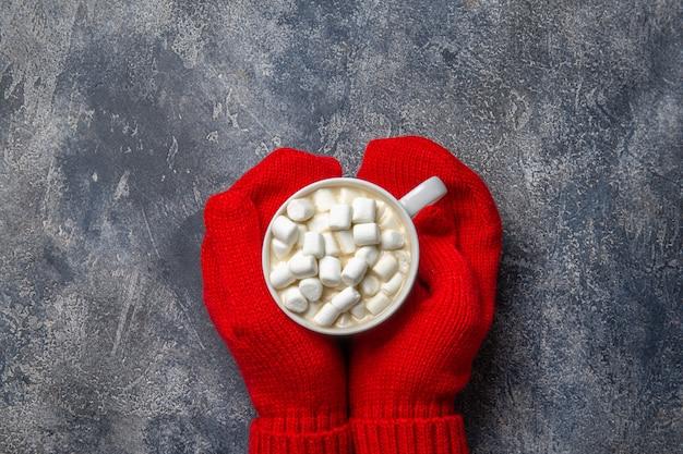 スカーフ、クリスマスと新年の居心地の良い休日組成、ミトンの女性の手、温かい飲み物と灰色のコンクリート背景にマシュマロのマグカップ。フラット横たわっていた、トップビュー。
