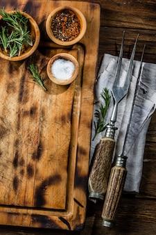 料理の背景のコンセプトです。カトラリーとビンテージのまな板。上面図