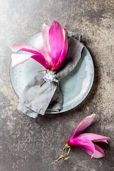 灰色のプレートに春のマグノリアの花とナプキン