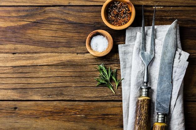 料理の背景のコンセプトです。ビンテージカトラリー、木製の背景にスパイス。