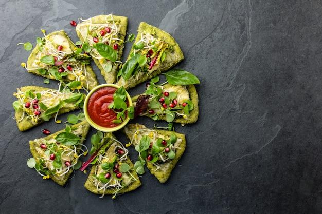 緑のほうれん草生地、野菜とチーズのピザ、スレートの背景