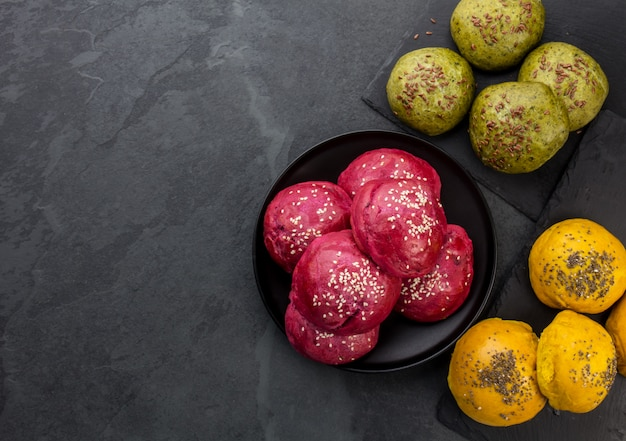 ハンバーガーのための健康的な自家製の色付きのパンパン。紫色のブートルート、緑のほうれん草と黄色のウコンハンバーガーパン、上面図、コピースペース。