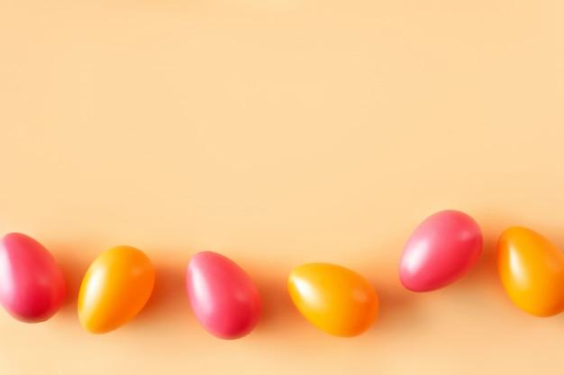 Плоская кладка оранжевых и красных пасхальных яиц