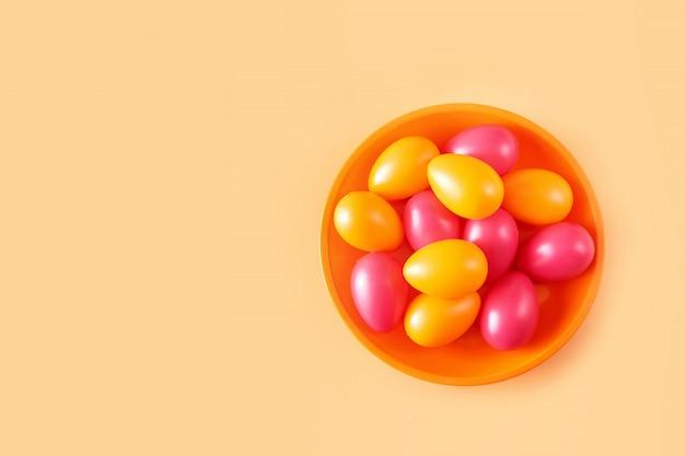 Оранжевые и красные пасхальные яйца в тарелке