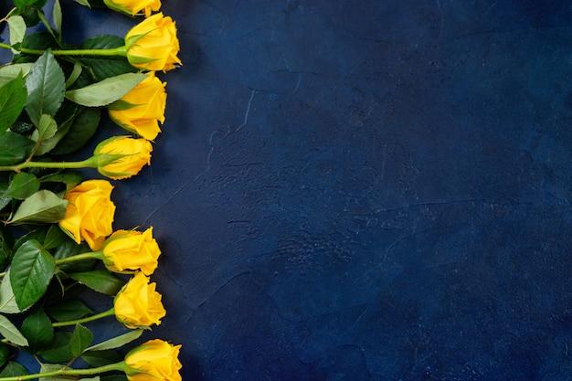 暗い青色の背景に美しい黄色のバラのトップビュー