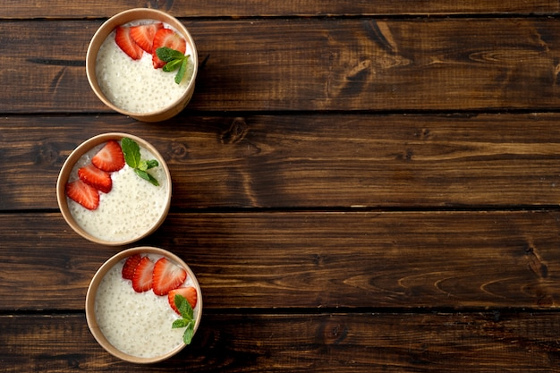 Три бумажных стаканчика крафт с пудингом из тапиоки с растительным молоком