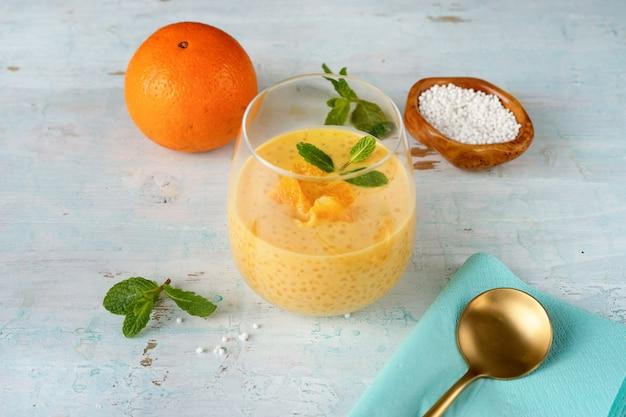 オレンジとビーガンのタピオカプディングとガラスのクローズアップ