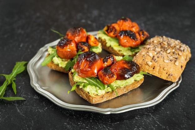 Вкусные веганские бутерброды с пюре из авокадо, жареными помидорами и рукколой